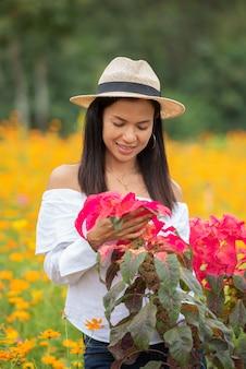 アジアの女性たちは公園で赤い花を楽しんでいます。