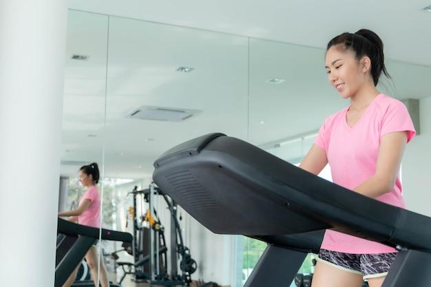 アジアの女性は体を健康に保つために革の水をふるいにかけるためにジムで運動しています。プレミアム写真