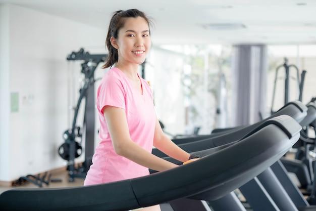 아시아 여성들은 몸을 건강하게 유지하면서 가죽 물을 걸러 내기 위해 체육관에서 운동하고 있습니다. 프리미엄 포토