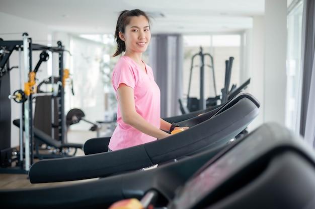 아시아 여성들은 몸을 건강하게 유지하면서 가죽 물을 걸러 내기 위해 체육관에서 운동하고 있습니다. 프리미엄 포토 프리미엄 사진