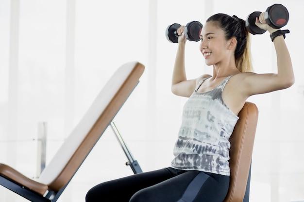 アジアの女性は体を健康に保つために革の水をふるいにかけるためにジムで運動しています。