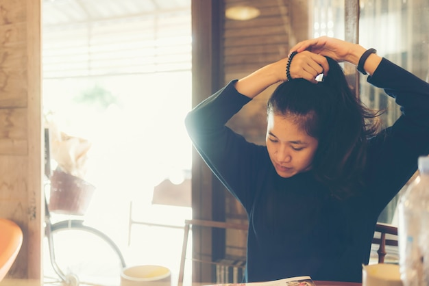 Asian women are gathering hair up to prepare themselves
