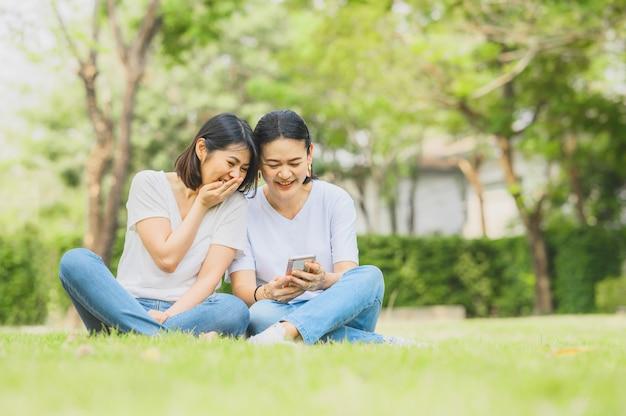 アジアの女性がスマートフォンを屋外で使用しながら笑っています Premium写真