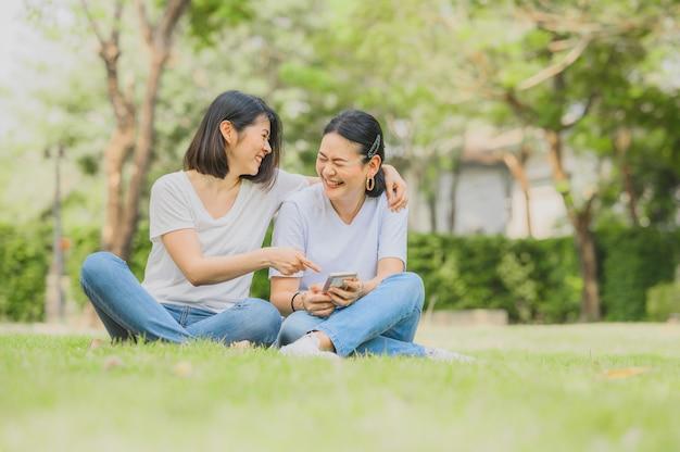 Азиатские женщины смеются при использовании смартфона на открытом воздухе