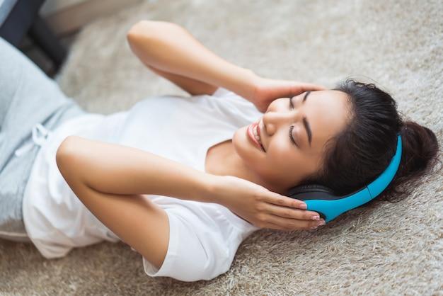 アジアの女性は音楽を聴いていて、彼女はカーペットの上で楽しく眠っている部屋で歌います