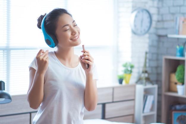 アジアの女性は音楽を聴いていて、彼女は楽しく部屋で歌います