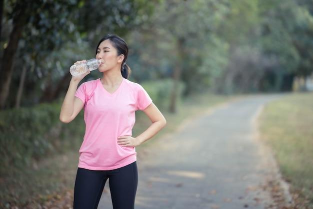 アジアの女性が飲料水を開いています