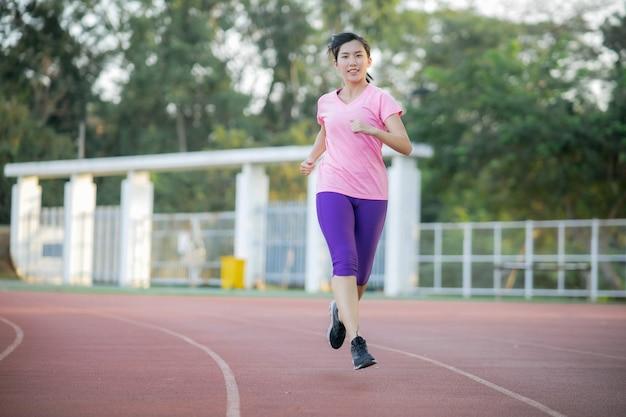 アジアの女性は、体重を減らして健康を維持するために公園を走っています。