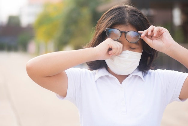 アジアの女性が屋外のアレルギーのためにまぶたを引っ掻いている女性はかゆみを持っています