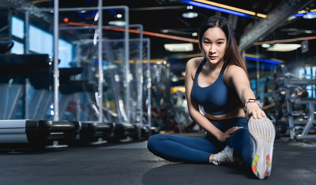 Asian women are sitting stretching their legs to stretch their muscles to warm up or cool down after a workout at fitness or gym with a patition barrier for social distancing in sport healthy concept.