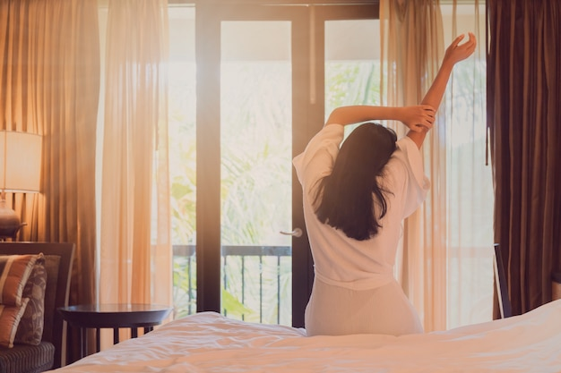 Asian women are staying in a hotel room after wake up on morning. open the curtain in the room looking to outside view.