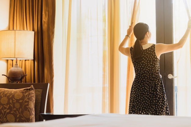 Asian women are staying in a hotel room.open the curtain in the room looking to outside view.