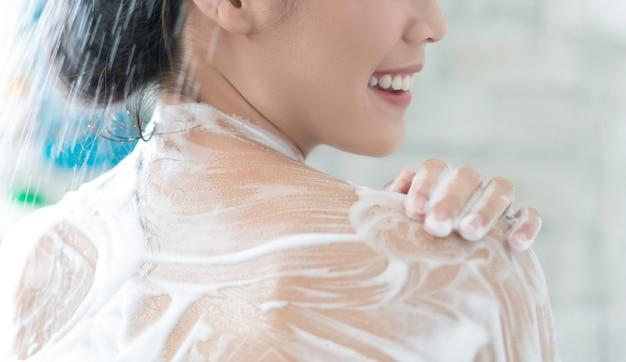 アジアの女性はトイレでシャワーを浴びている彼女は石鹸を擦っている、彼女は彼女を背負っている
