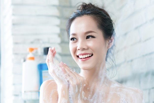 Asian women are taking a shower in the bathroom she is rubbing soap,she is happy and relax