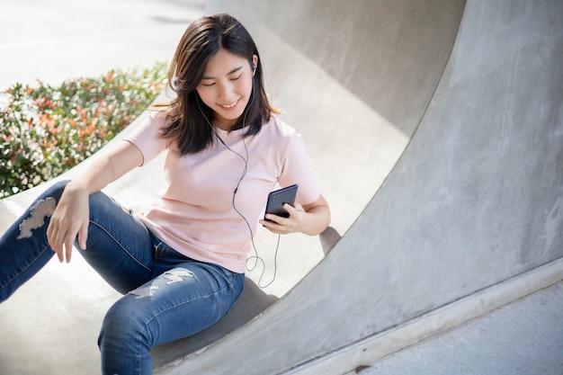 アジアの女性は携帯電話で働いて音楽を聴いています。