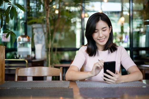 Asian women are working and listening to music on mobile phones.