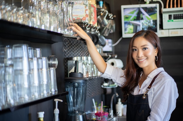 Asian women barista smiling and using coffee machine in coffee shop counter - working woman small business owner food and drink cafe