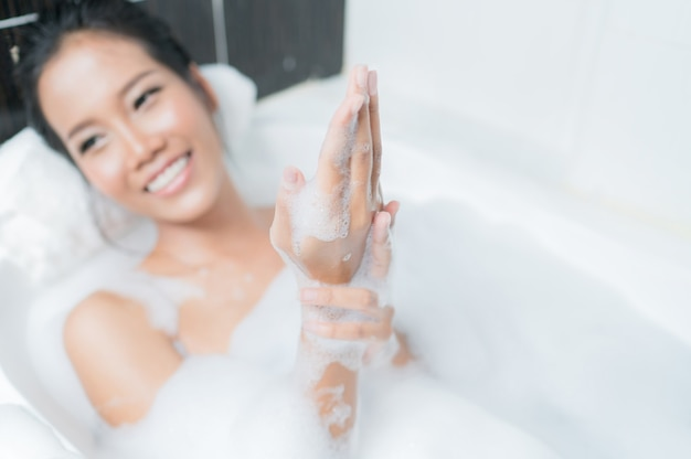 Asian women bathing in the bathtub she was rubbing the soap on her hands