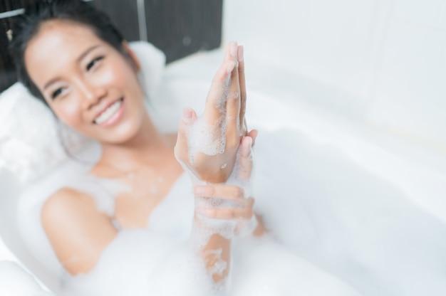 アジアの女性バスタブで入浴彼女は彼女の手に石鹸をこすっていた