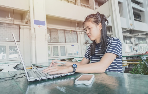 Asian women be working with notebook on the table in university area. she look stress and calm work.