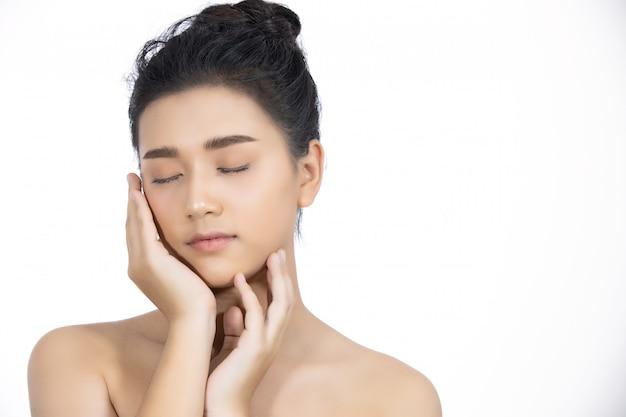 깨끗하고 신선한 피부를 가진 아름다운 아시아 여성 터치 자신의 얼굴. 페이셜 트리트먼트. 코스 메토 로그