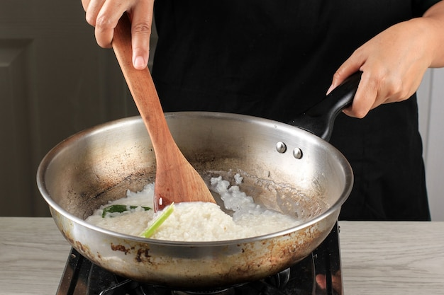 Азиатские женщины варят клейкий рис на сковороде на кухне. размешайте клейкий рис деревянной лопаткой