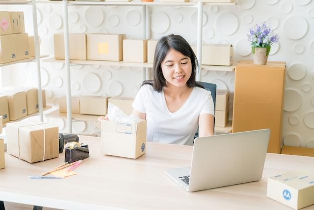 Владелец бизнеса азиатских женщин, работающих дома с упаковочной коробкой на рабочем месте - онлайн-шоппинг или продажа онлайн-концепции