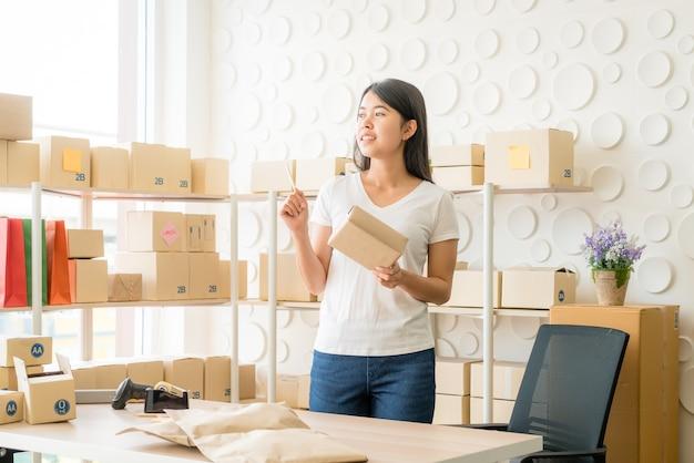 직장에 포장 상자와 함께 집에서 일하는 아시아 여성 비즈니스 소유자-온라인 쇼핑 중소기업 기업가 또는 프리랜서 작업 개념