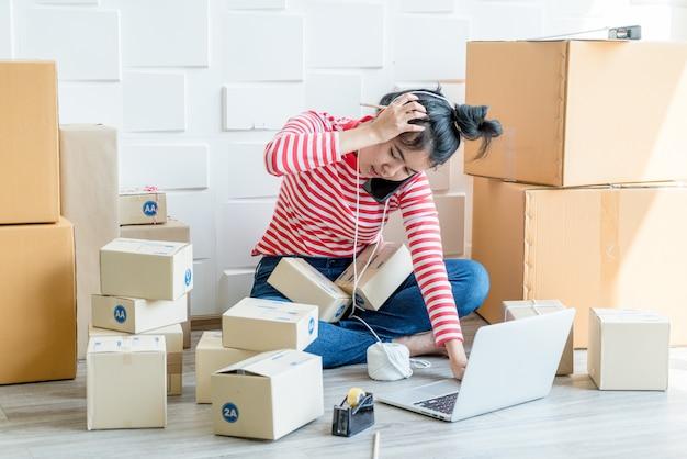 직장에 포장 상자와 함께 집에서 일하는 아시아 여성 비즈니스 소유자