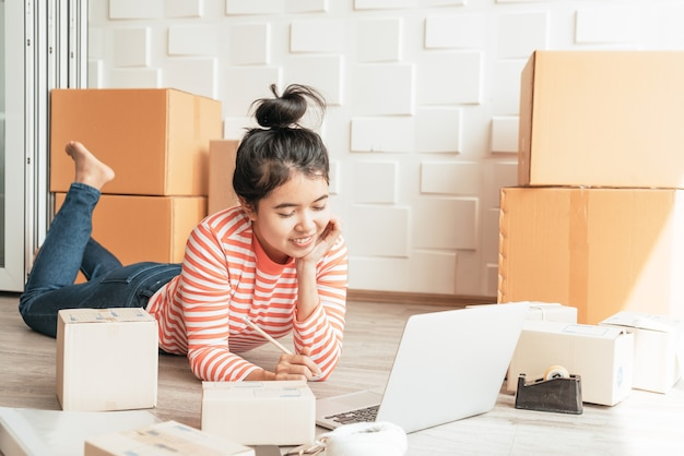 Asian women business owner working at home with packing box on workplace - online shopping sme entrepreneur or online selling concept