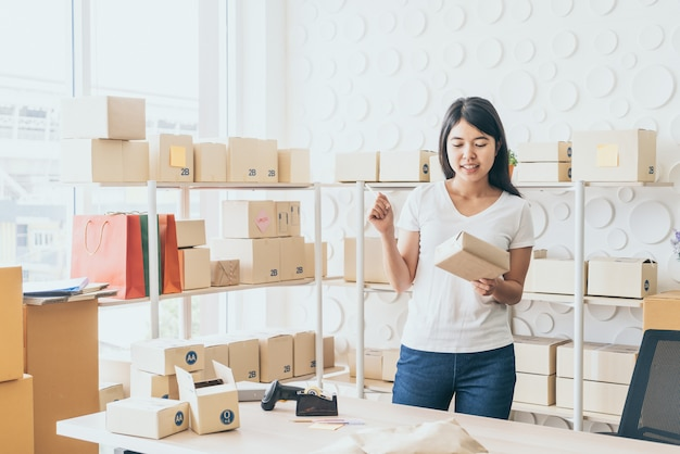 Asian women business owner working at home with packing box on workplace
