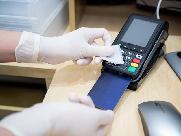 Asian women at cashier counter use alcohol pad to clean credit card terminals or machine before swiping client card, prevent spreading of coronavirus. covid-19, coronavirus, social distance concept.