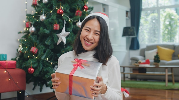 Asian women celebrate christmas festival. female teen wear sweater and christmas hat relax happy hold gift smiling near christmas tree enjoy xmas winter holidays together in living room at home.