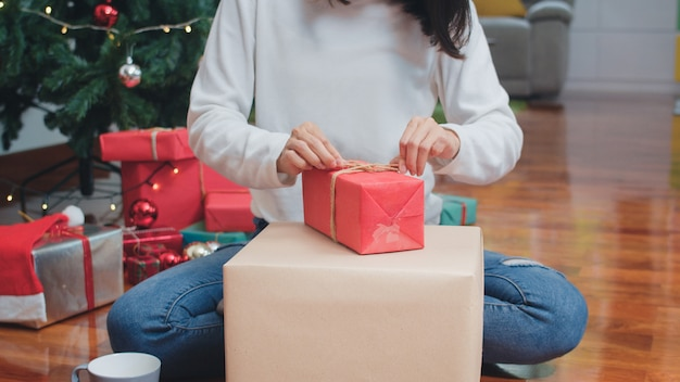Asian women celebrate christmas festival. female teen wear sweater and christmas hat relax happy wrapping gifts near christmas tree enjoy xmas winter holidays together in living room at home.