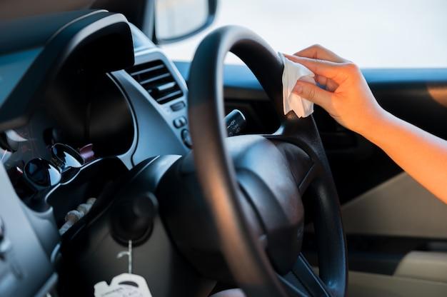 アジアの女性は、コロナウイルスを防ぐためにアルコールジェルで車のインテリアを掃除します