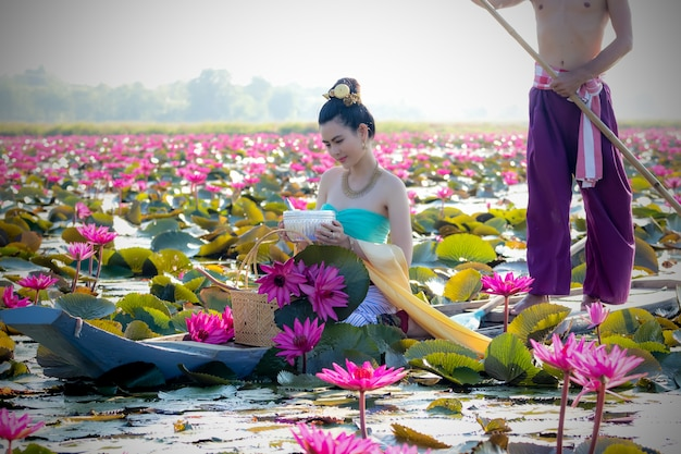 Asian women collecting red lotus to bring to worship with the monks on a religious day.