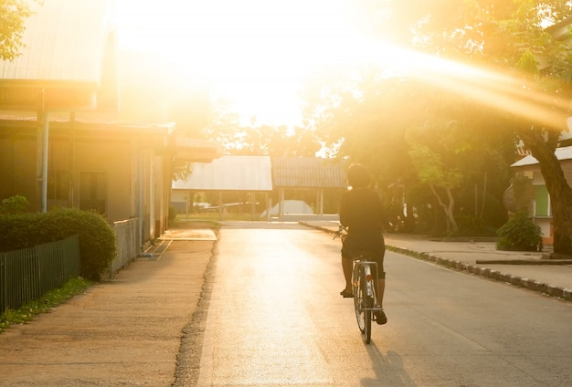 Asian women cycling on street in evening light at alone