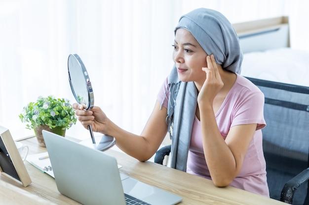 머리 스카프를 두른 분홍색 리본이 달린 거울을 보고 있는 아시아 여성의 유방 암 환자 여성, 집에 있는 노트북에서 일하는 비즈니스로 화학 요법 치료를 받은 후, 의학 개념