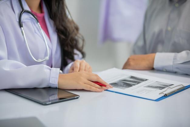 아시아 여성 의사와 남성 환자는 진료소에서 결과 엑스레이 이미지에 대해 토론합니다.