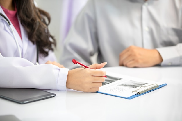 Asian women doctor and man patient discussion about  result x-ray images in clinic office