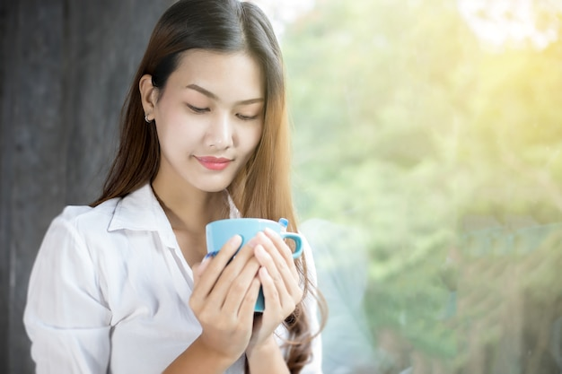 Asian women drinking coffee on morning sunshine