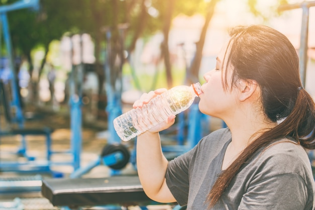 Asian women drinking water in hot day outdoor exercise in the park