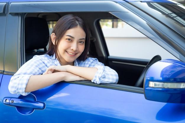 여행을 여행하는 동안 운전 중에 기쁜 긍정적 인 표정으로 차를 운전하고 행복하게 미소 짓는 아시아 여성, 사람들은 웃고있는 교통을 즐기고 개념을 통해 운전