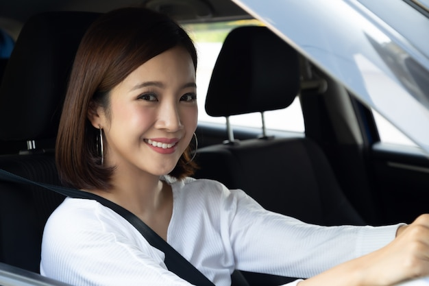 Азиатские женщины управляют автомобилем и радостно улыбаются с радостным позитивным выражением во время поездки, люди наслаждаются смехом и расслабленной счастливой женщиной, путешествующей по дороге.