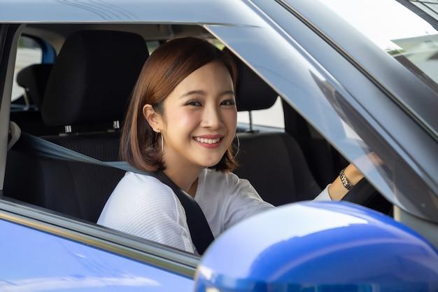 차를 운전하고 행복하고 미소 짓는 아시아 여성.