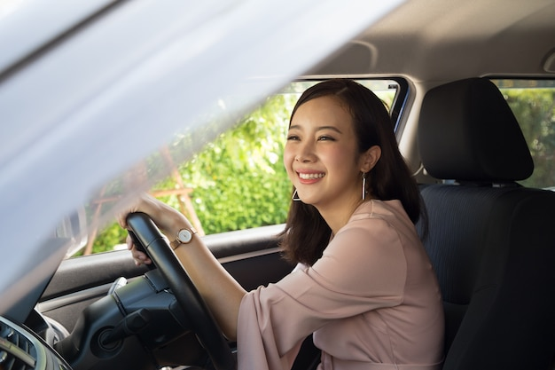 Asian women driving a car and smile happily with glad positive expression