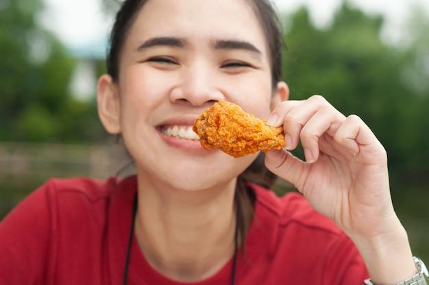 테이블에 앉아 닭 날개를 먹는 아시아 여성