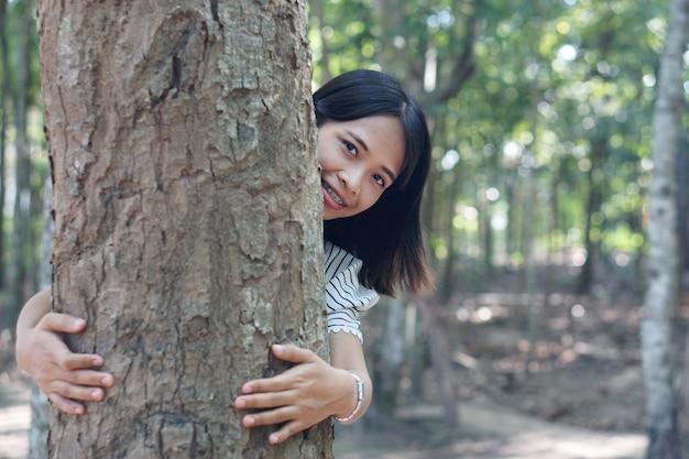 아시아 여성은 사랑, 세계에 대한 사랑의 개념으로 나무를 포용합니다.