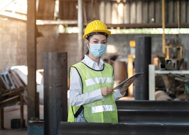 Covid-19パンデミック時に工場内の汚染とウイルスを保護するために安全マスクを着用して工場ステーションでの生産プロセスをチェックするアジアの女性エンジニア