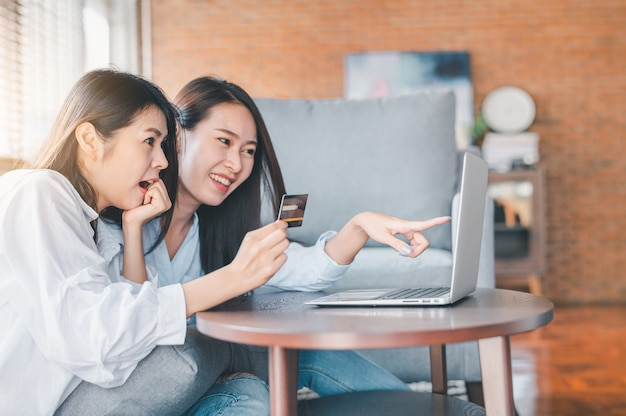 Asian women exciting while using credit card for online shopping